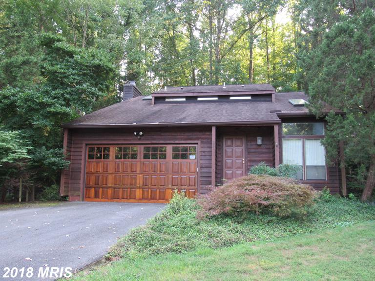 Beautifully landscaped contemporary home located on wooded acre. Two story cathedral ceiling in livi